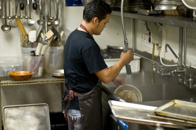 man washes dishes at a restaurant