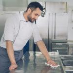 man maintains equipment in restaurant